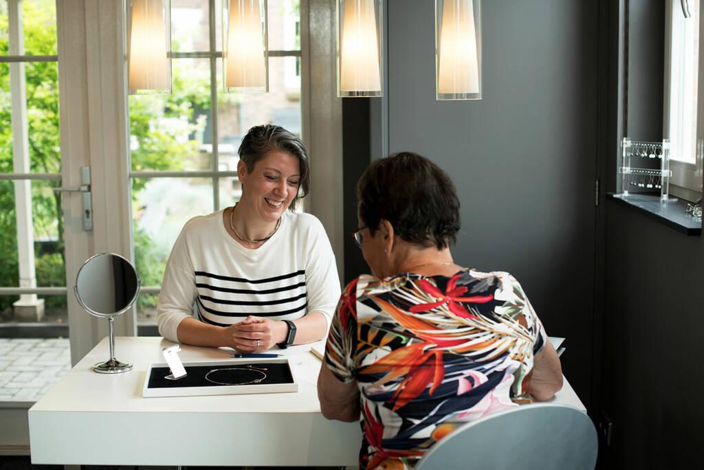 Edelsmid Marita van Oorschot in gesprek met klant over ontwerp uniek sieraad